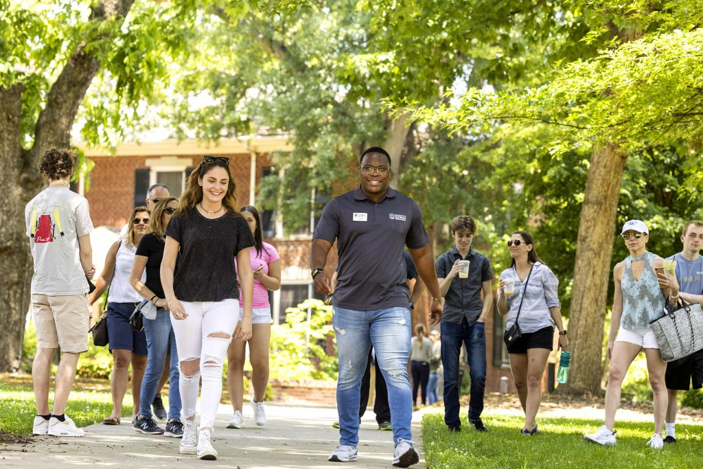 Zerian Hood leads a tour of people on college campus