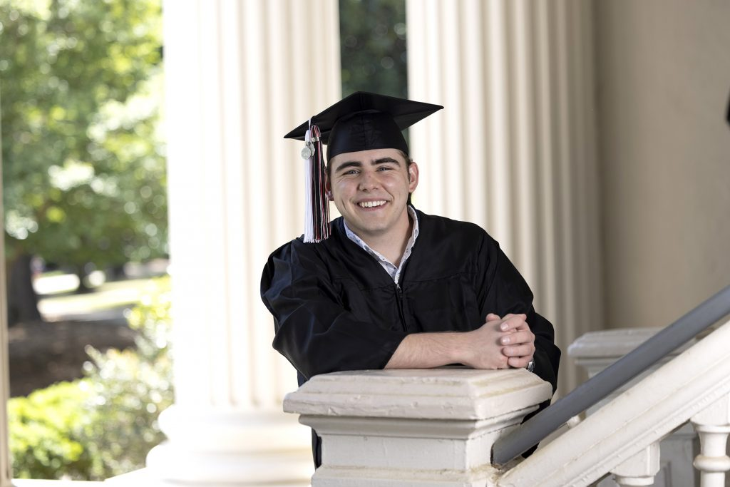 Chan Creswell in cap and gown shown in front of columns on North Campus.
