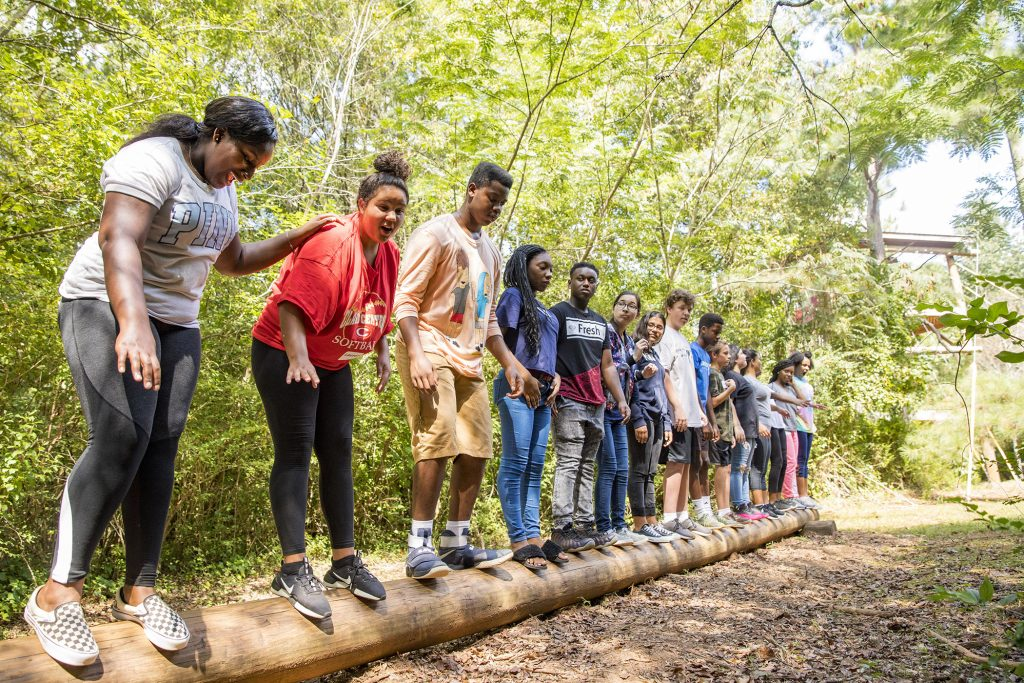 Group of students standing on a log on an outdoor ropes course.