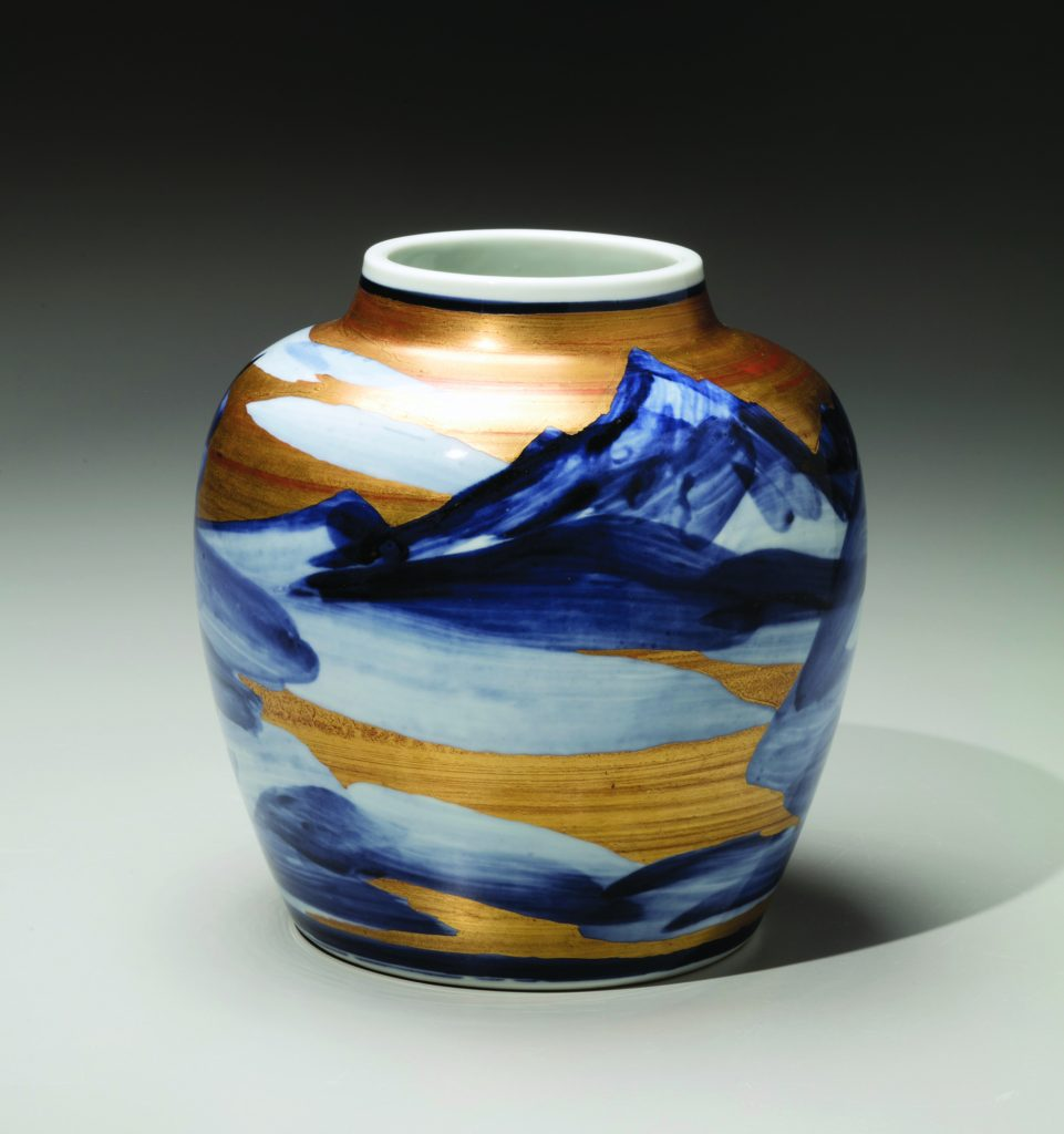 Blue and gold vase with mountains and clouds painted on it.