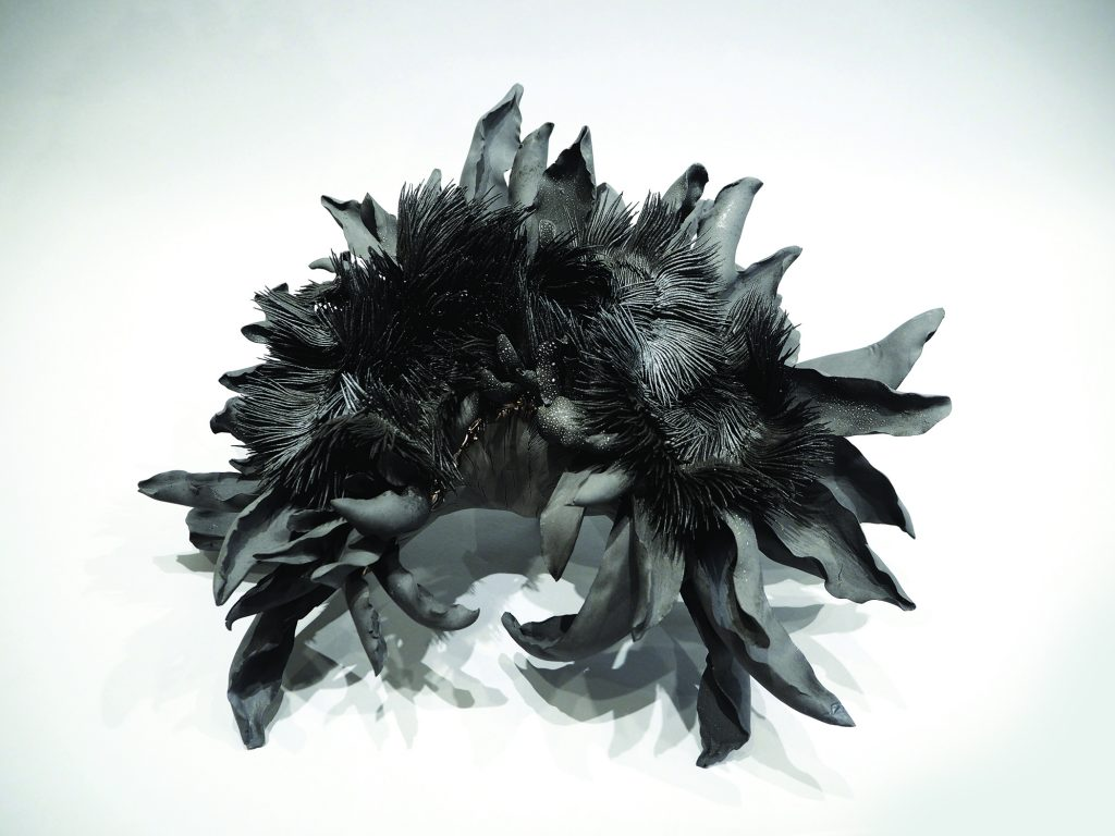 Abstract piece of ceramic art with black feathers.