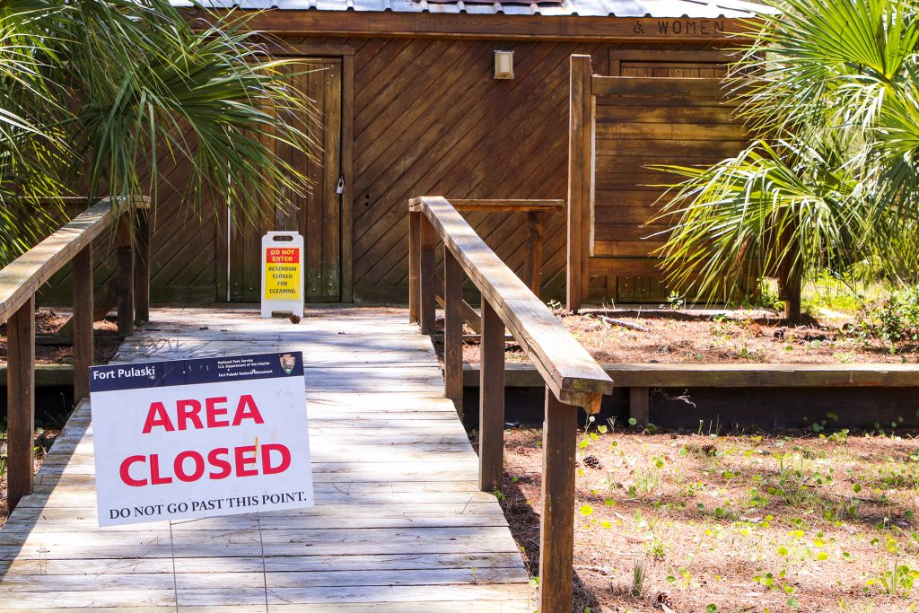 A sign posted outside a bathroom facility says area closed.