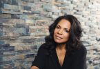 Audra McDonald poses in front of a brick wall.
