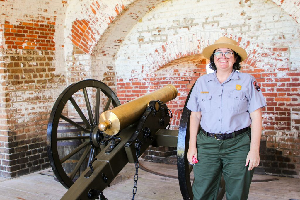 A uniformed female stands next to an old cannon.
