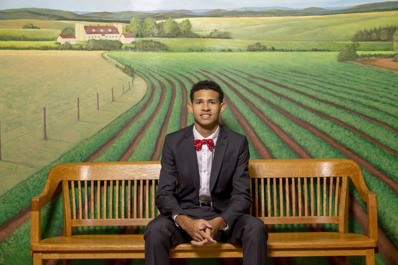 Jay Ivey, wearing a suit and bow tie, sits on a bench in front of a mural of farmland.