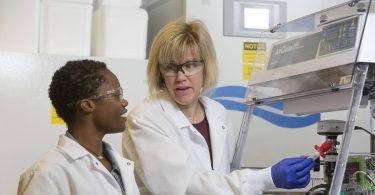 Karen Burg (right) talks to Kristen Allen (left). Both women are wearing white lab coats and safety glasses.