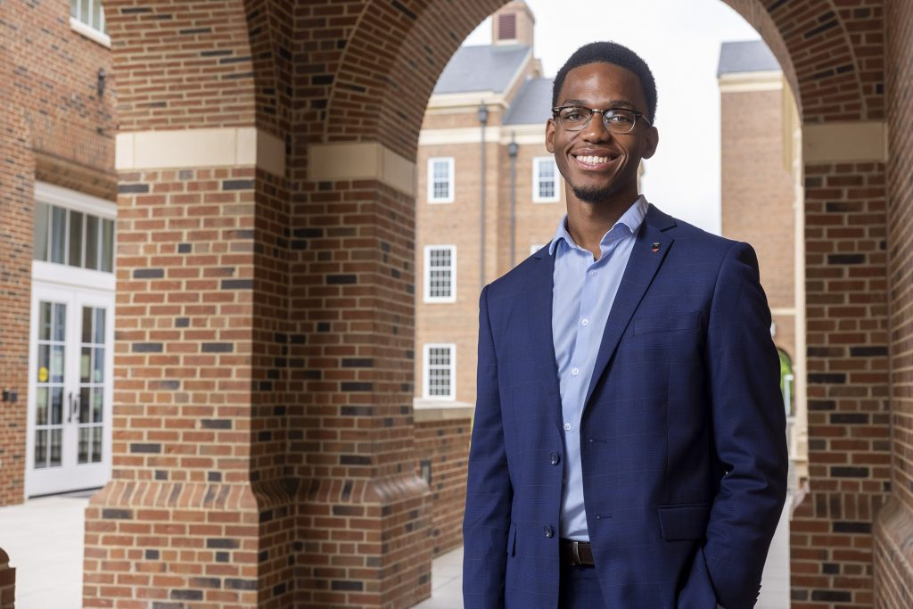 Portrait of Kevin Nwogu wearing a suit standing in the Business Learning Community,