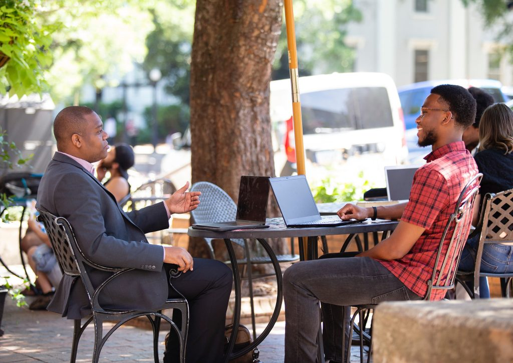 Kevin Nwogu and Raymond Phillips talk outside at a table.