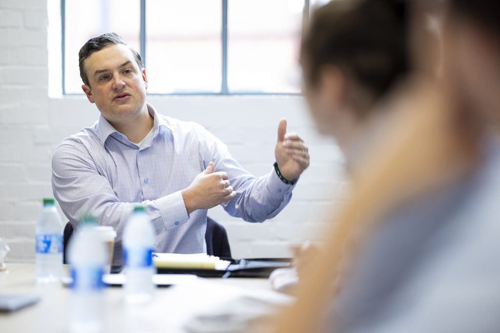 Scott Edwards talks with interns in an office