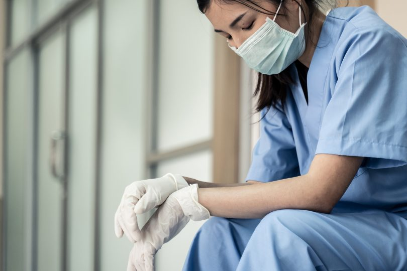 Woman in scrubs and a mask looking tired.