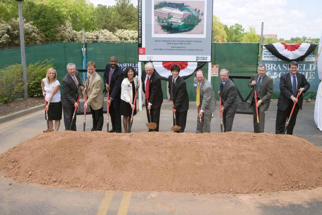 Eleven people pose with shovels at a groundbreaking