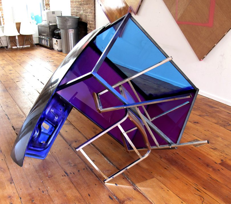 A purple and blue sculpture made of plexiglass and a chair.