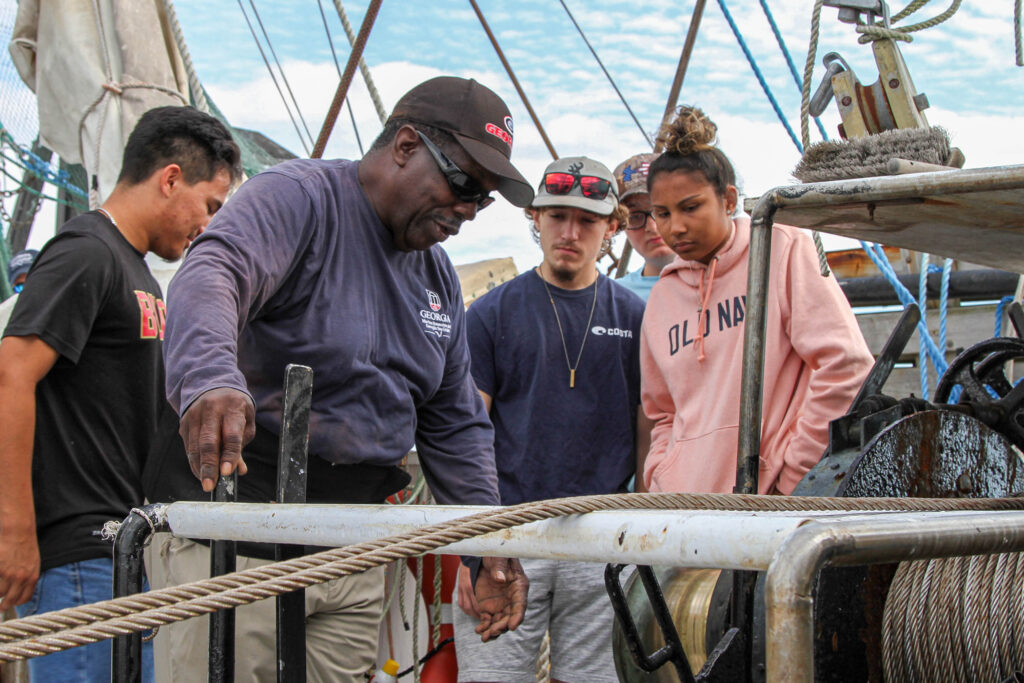 Herbert Truck McIver demonstrates for students how equipment is used on a commercial fishing vessel
