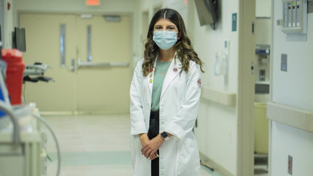 Portrait of Aliya Abdulla in a hospital hallway way, wearing a face mask.