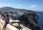 A student sitting on a wall overlooking Greece.