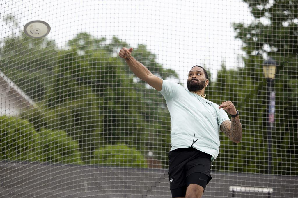 Devon Williams throws a discuss outdoors on a track.