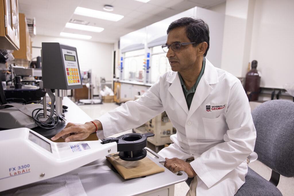 Professor Gajanan Bhat runs an elastic nonwoven material through a permeability tester inside his lab.