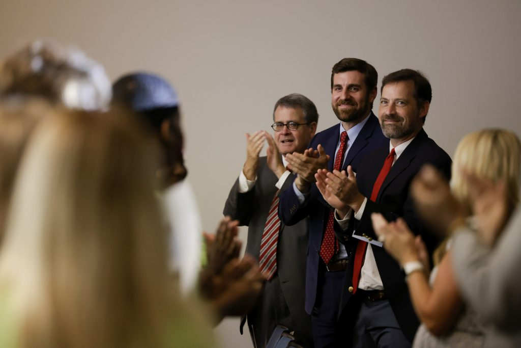 Three UGA administrators and audience members applaud the students after they made their presentations.