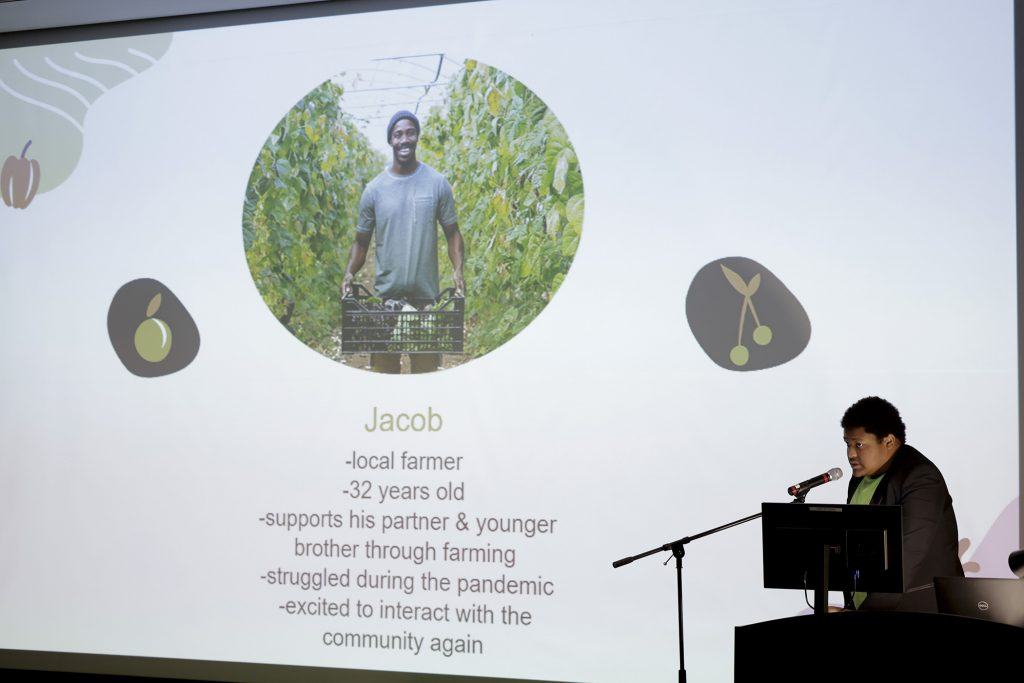 A student talks into a microphone during a presentation with a slide of another student on the screen behind him.