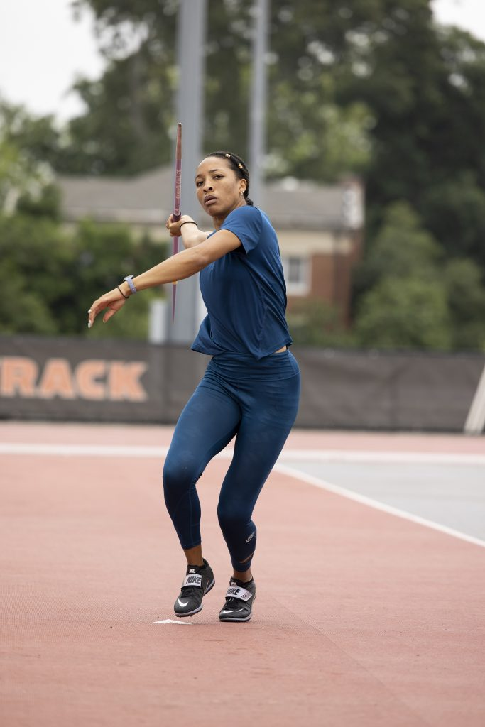 Kendell Williams throws a javelin on an outdoor track field.