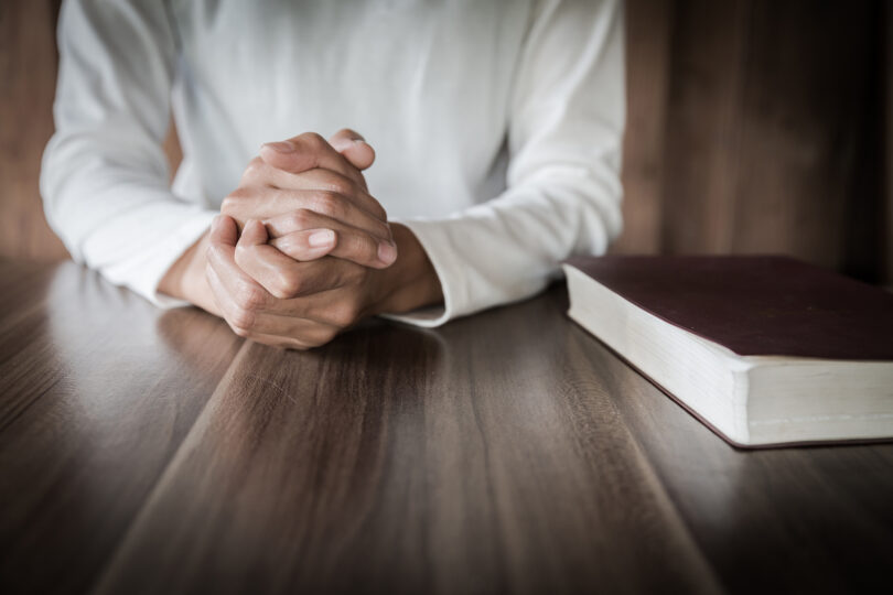 A photograph of a minister's hands and a bible.