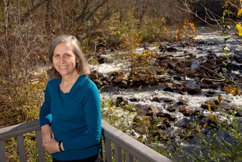 Portrait of Pamela Orpinas standing on a deck near a river