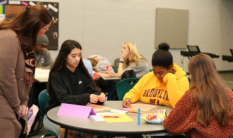 Three students sitting at a table working on a leadership project.