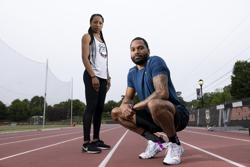 endell and Devon Williams pose on an outdoor track.