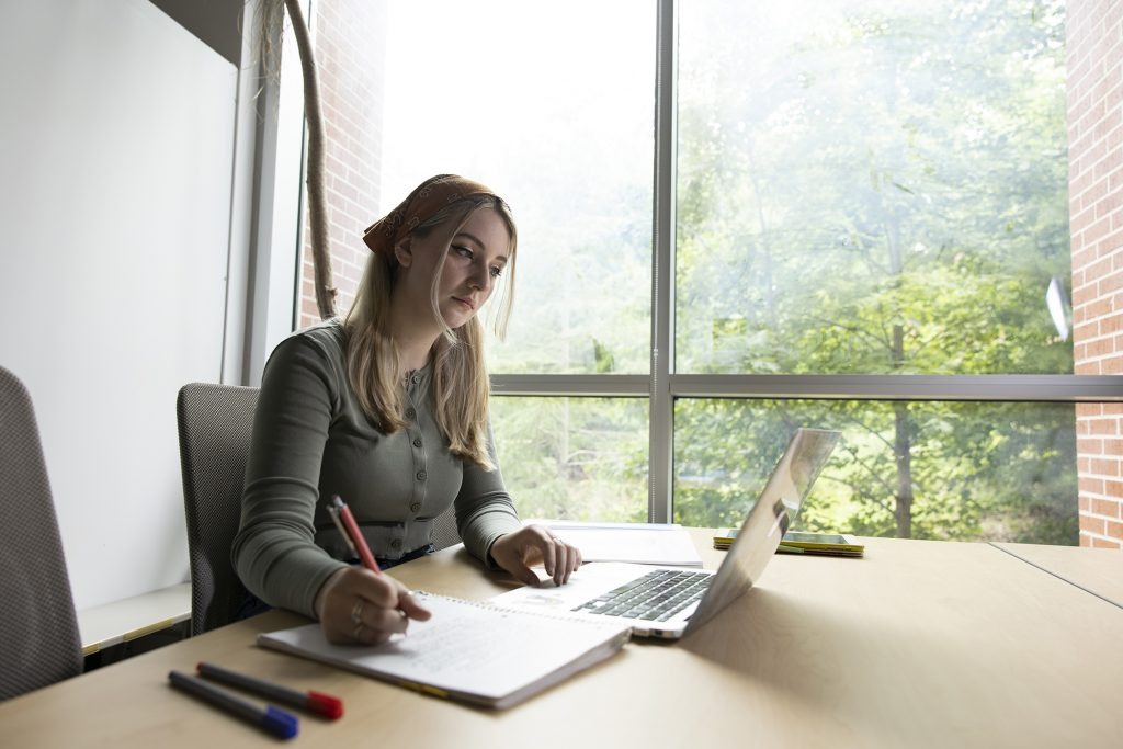 Tori Watson studying at a desk with a laptop.