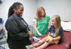 A health care worker talks with a child patient in a doctor's office.