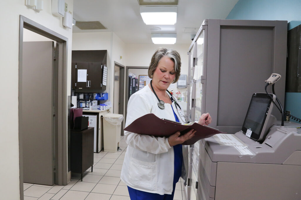 A health care worker reads over a patient's chart.
