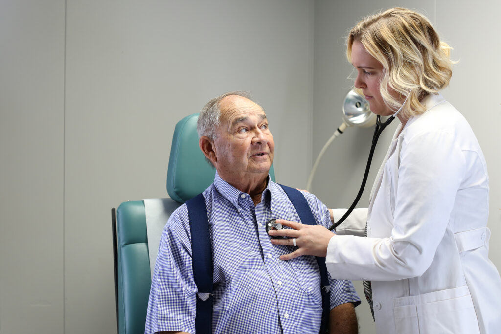A nurse checks a patient's heartbeat with a stethoscope.