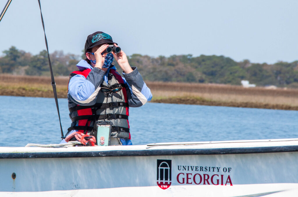 A person looks over the water using binoculars.