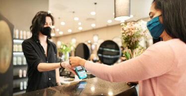 A woman at a hair salon pays contactless while wearing a protective face mask.