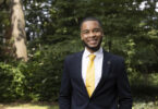 Portrait of Eric Okanume outdoors. He is wearing a suit with a yellow tie.