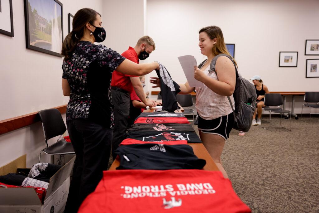 A woman hands a student a T-shirt after she got her vaccine.