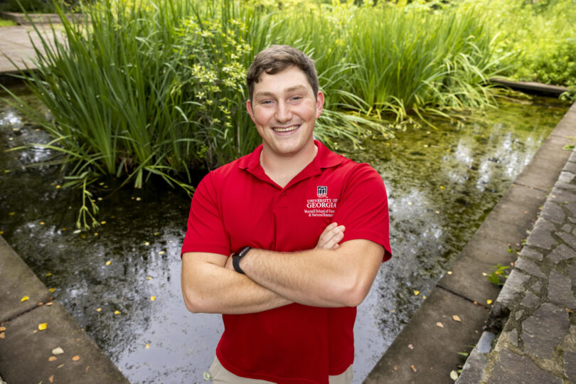 Seamus OBrien poses in front of a turtle pond.
