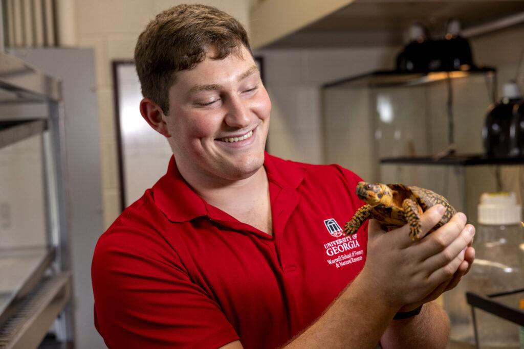 Seamus O'Brien holds a box turtle.