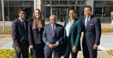 Four law students stand with Georgia Supreme Court Justice Robert Benham in the center.