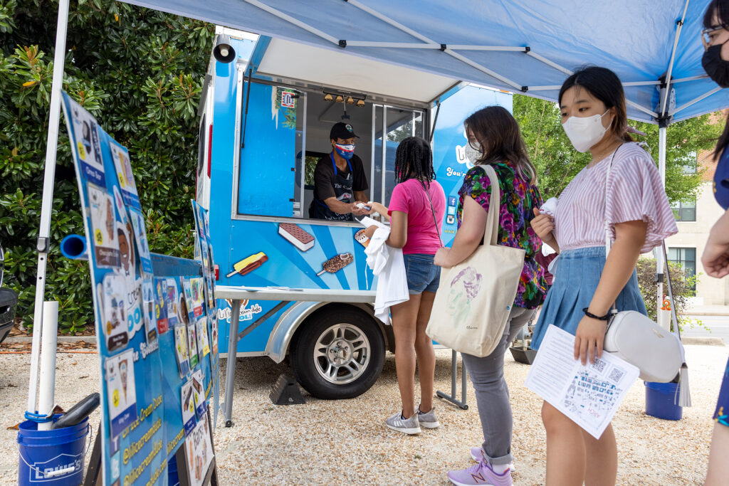 college students outside in masks line up at an ice cream truck.