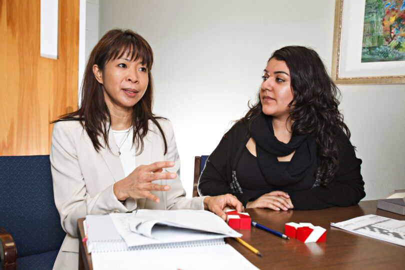 Bernadette Heckman talks with a student in her office.