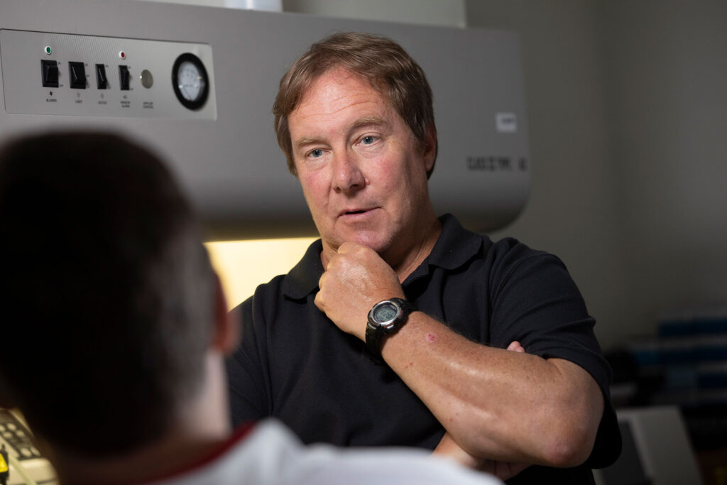Researcher Ralph Tripp talks with a scientist on his team in front of lab equipment