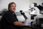 Researcher Ralph Tripp sits in front of a microscope