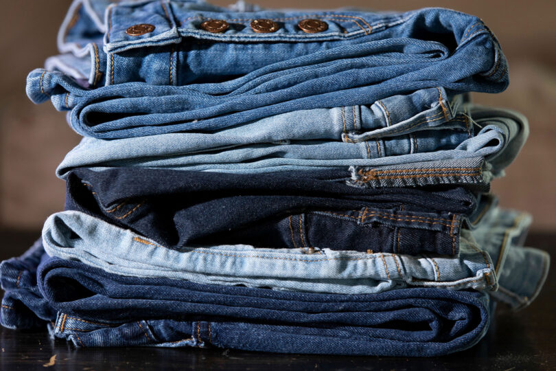 A stack of different colored jeans