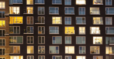People are shown in the windows of their units in a large apartment building at dusk.