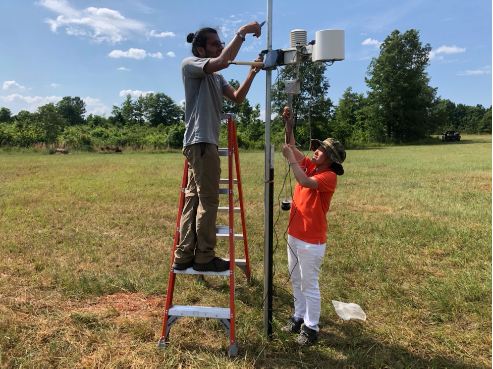 Two people assemble a small weather station on a peach farm.