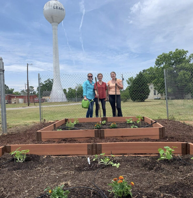 Three people stand behind newly planted raised garden beds.