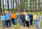 A group of attendees stand for a photo in fronta line of trees.