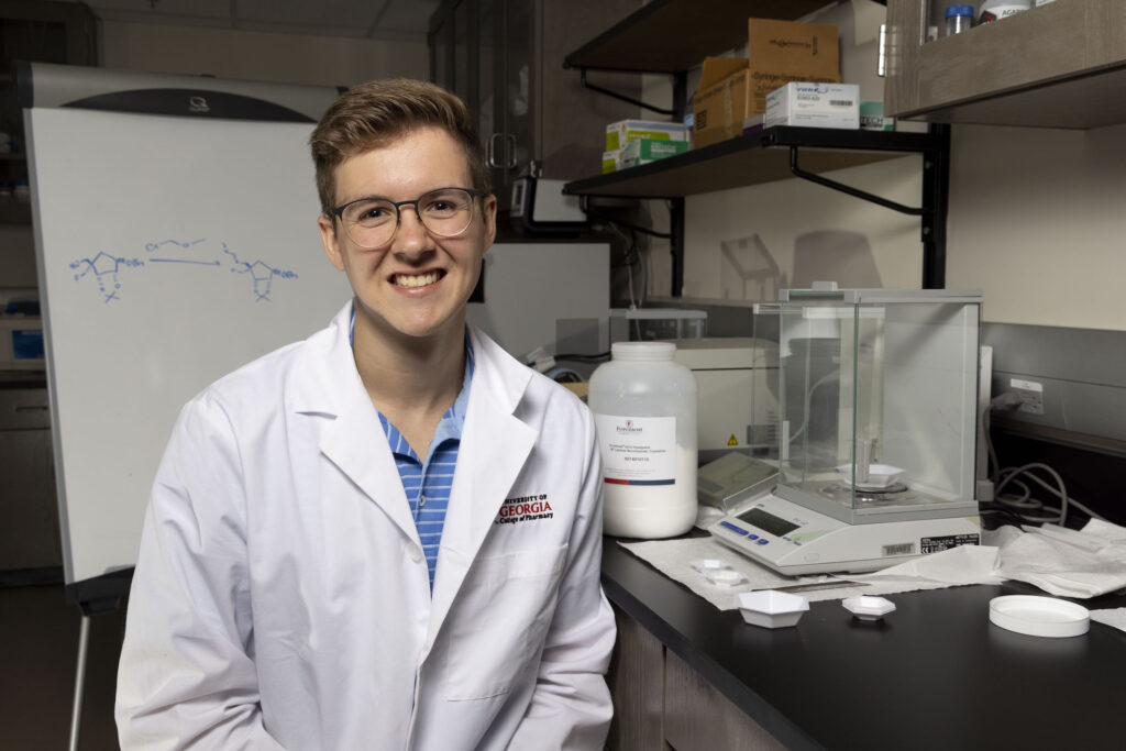 Portrait of student Ransom Jones wearing a lab coat in a lab.