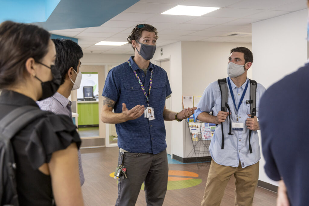 A doctor speaks to students in a medical facility setting.